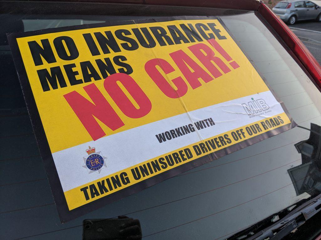 A 'No Insurance' sticker on a windscreen