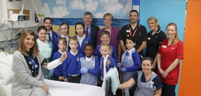 Longfleet Road School teacher and schoolchildren, together with David Moss, chairman and Debbie Fleming, chief executive, (both back centre), and other members of hospital staff, at the opening of the new facility
