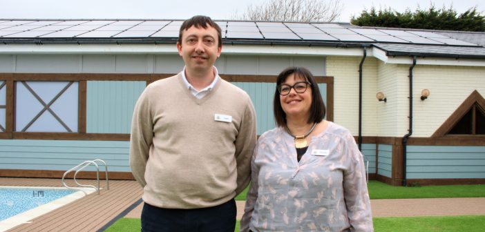 image of Justin Smith and Miranda Jacobs with solar panels at one of The Waterside Holiday Group's parks