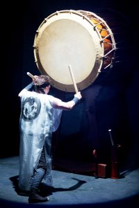 image of Taiko drummer drumming on a large drum