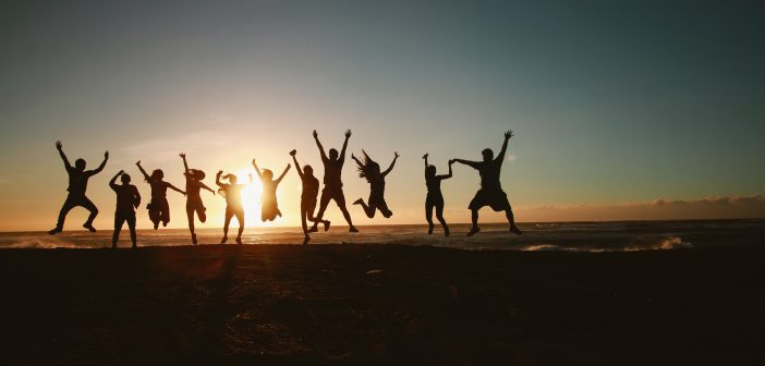 image of silhouettes of people celebrating in front of a sunset