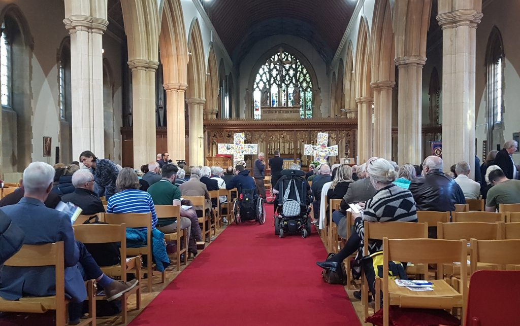 image of people seated inside the church for the debate