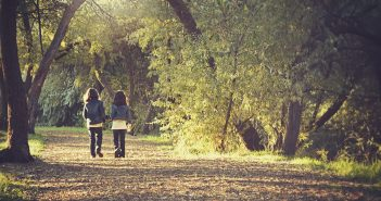 image of two children walking through a woodland path