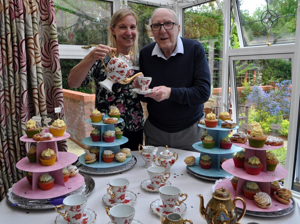 image of Heather Lawrence at tea with one of the care home's residents