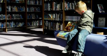 image of boy reading in a library